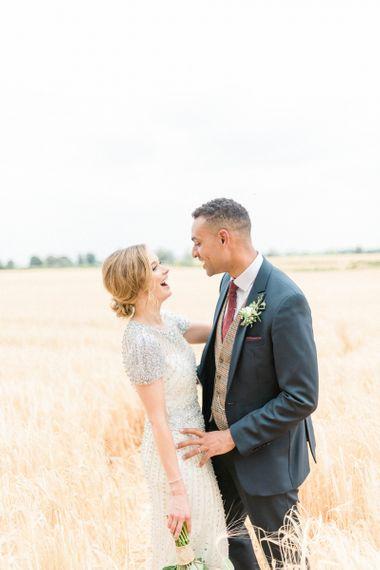 Laughing Bride in Beaded Wedding Dress and Groom in Dark Suit & Check Waistcoat