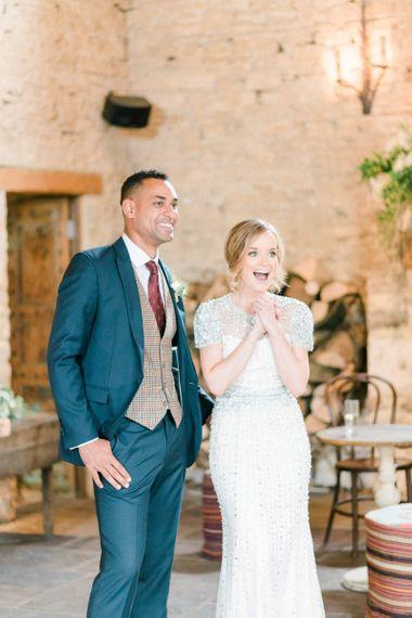 Ecstatic Bride in Beaded Wedding Dress and Groom in Dark Suit & Check Waistcoat