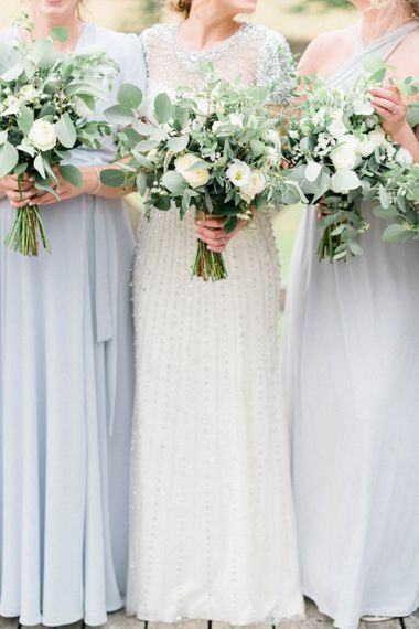 Bride and Bridesmaids Holding White and Foliage Wedding Bouquets