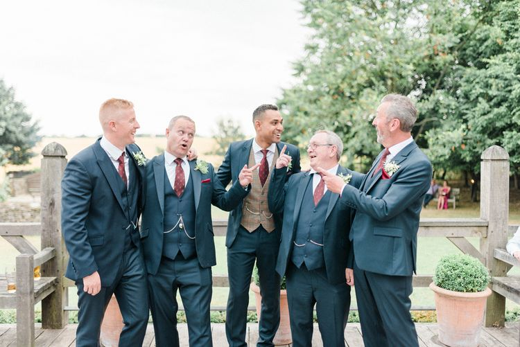 Groomsmen in Dark Suits from Whitfield & Ward with the Groom Wearing a Check Waistcoat and Burgundy Tie