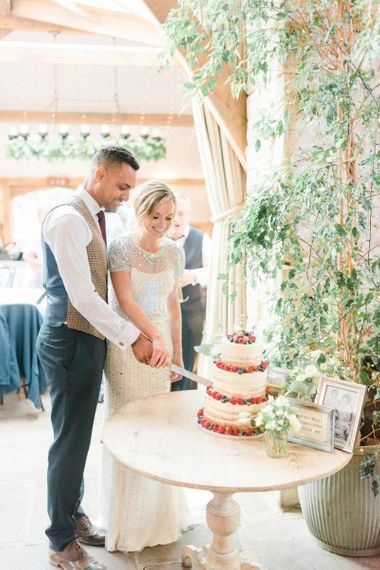 Bride in Beaded Wedding Dress and Groom in Dark Suit & Check Waistcoat Cutting the Wedding Cake
