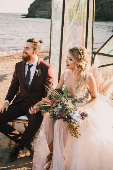 Bride and groom sat on beach