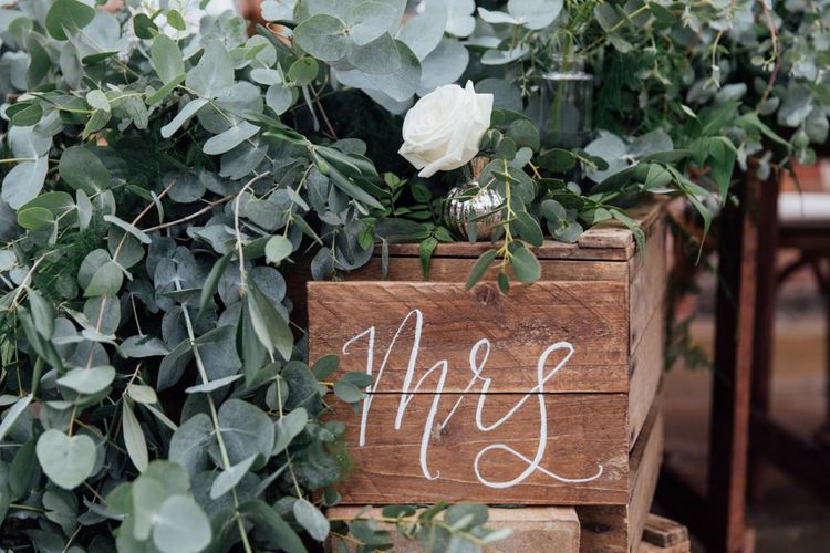 Top Table Heavy Eucalyptus Foliage with White Roses | DIY Pallet Signage | White Calligraphy | French Rustic at Northbrook Park in Surrey | Images by Charlotte Bryer-Ash