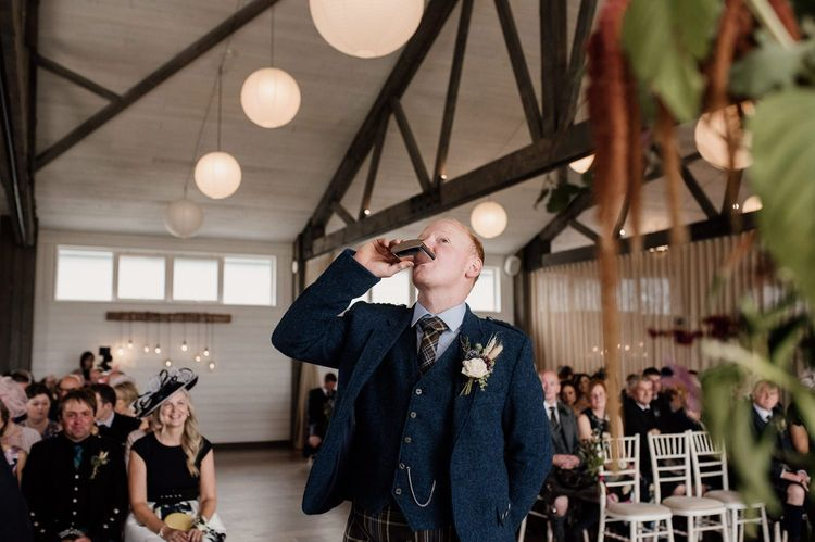 Groom in tartan kilt and wool jacket drinking from a hip flask at the altar