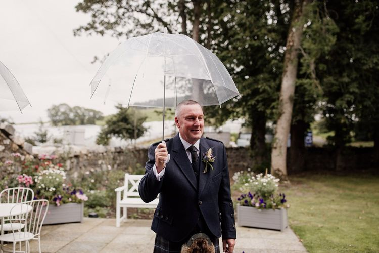 Father of the bride holding a clear umbrella by Aberdeen wedding photographer
