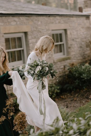 Bride in Long Sleeved Andrea Hawkes Dress with Bateau Neck and Low V-Back with Buttons | Bridesmaid in Forest Green Reformation Dress with Long Sleeves | Wedding Bouquets with Eucalyptus, White Roses, White and Blue Thistles and Ferns | Emerald Green Bridesmaid Dress for a Winter Wedding at Middleton Lodge | Georgina Harrison Photography