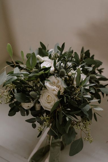Bridal Bouquet with Eucalyptus, White Roses, White and Blue Thistles and Ferns | Emerald Green Bridesmaid Dress for a Winter Wedding at Middleton Lodge | Georgina Harrison Photography