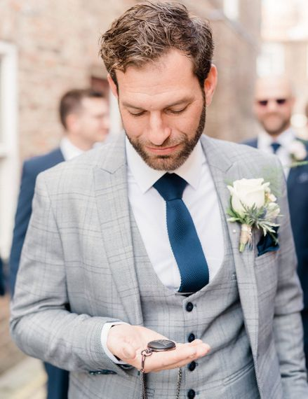 Groom in grey check suit with horseshoe waistcoat and navy tie