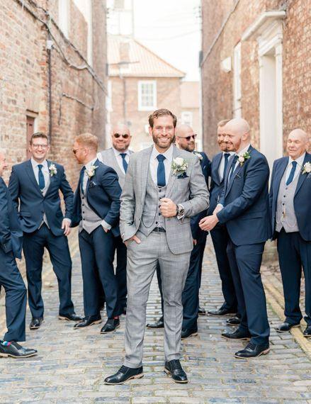 Groomsmen portrait with groom in grey suit and groomsmen in navy suits