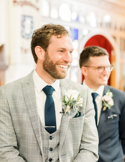 Groom smiling at the altar