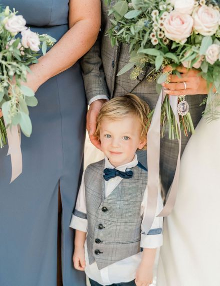 Page boy in grey waistcoat and navy bow tie