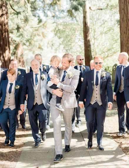 Groom holding his son and an entourage of groomsmen