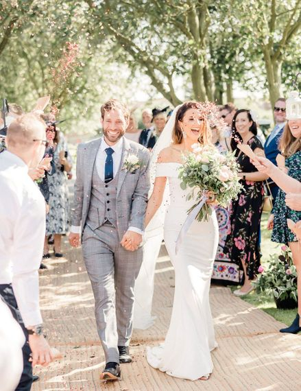 Confetti moment with groom in grey check suit and bride in off the shoulder wedding dress