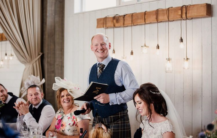 Groom in tartan kilt and wool waistcoat giving his wedding speech