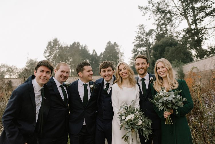 Bride in Long Sleeved Andrea Hawkes Dress with Bateau Neck and Low V-Back with Buttons | Groom in Navy Three-Piece Suit from Suit Supply with Green Tie | Bridesmaid in Forest Green Reformation Dress with Long Sleeves | Wedding Bouquets with Eucalyptus, White Roses, White and Blue Thistles and Ferns | Groomsmen in Navy Marks & Spencer Suits with Green Ties | Emerald Green Bridesmaid Dress for a Winter Wedding at Middleton Lodge | Georgina Harrison Photography