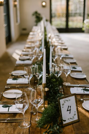 Wooden Banquet Tables | Foliage Table Runners | White Tapered Candles | Gold Candlesticks | Gold Tea Light Holders | Gold Framed Table Number | Emerald Green Bridesmaid Dress for a Winter Wedding at Middleton Lodge | Georgina Harrison Photography