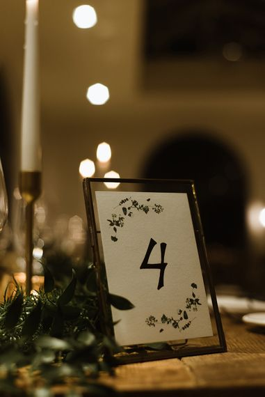 Table Number in Gold Frame | White Tapered Candle | Gold Candlestick | Emerald Green Bridesmaid Dress for a Winter Wedding at Middleton Lodge | Georgina Harrison Photography