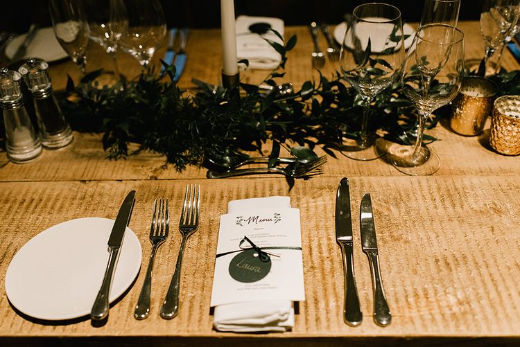 Wedding Breakfast Menu Tied with Ribbon | Foliage Table Runners | White Tapered Candles | Gold Candlesticks | Gold Tea Light Holders | Emerald Green Bridesmaid Dress for a Winter Wedding at Middleton Lodge | Georgina Harrison Photography