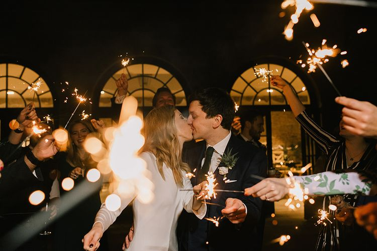 Bride in Long Sleeved Andrea Hawkes Dress with Bateau Neck and Low V-Back with Buttons | Groom in Navy Three-Piece Suit from Suit Supply with Green Tie | Sparkler Send Off | Emerald Green Bridesmaid Dress for a Winter Wedding at Middleton Lodge | Georgina Harrison Photography