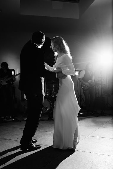 Bride in Long Sleeved Andrea Hawkes Dress with Bateau Neck and Low V-Back with Buttons | Groom in Navy Three-Piece Suit from Suit Supply with Green Tie | First Dance | Emerald Green Bridesmaid Dress for a Winter Wedding at Middleton Lodge | Georgina Harrison Photography