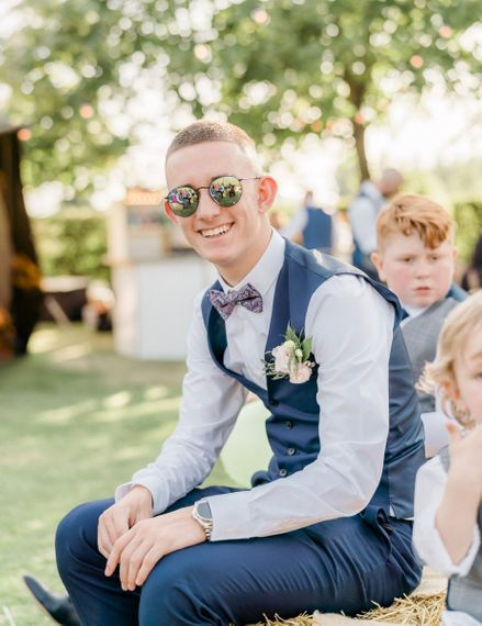 Groom in navy suit, bow tie and sunglasses at summer teepee wedding
