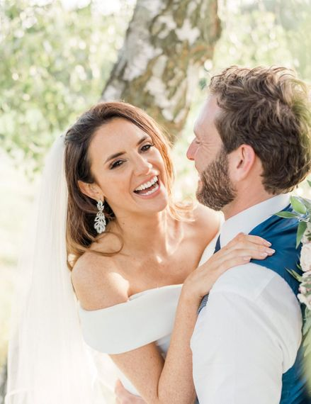 Bride in Bardot wedding dress and chandelier earrings laughing