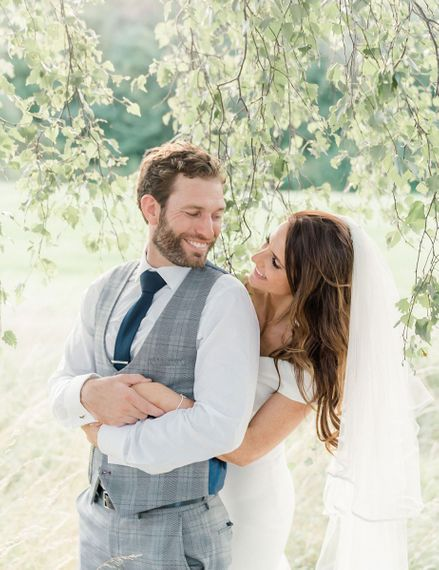 Bride embracing her husband in a grey check suit with navy tie