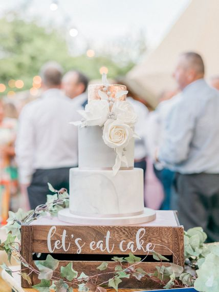 Marble wedding cake with copper layer on a wooden crate cake stand
