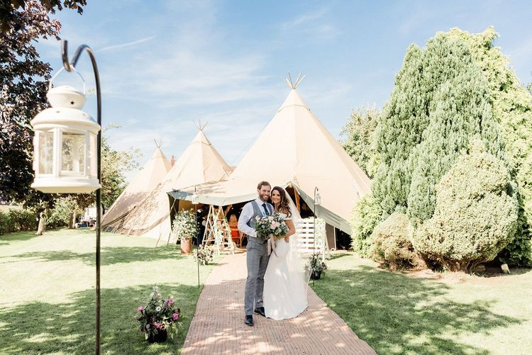 Bride and groom portrait standing in from of their teepee wedding reception