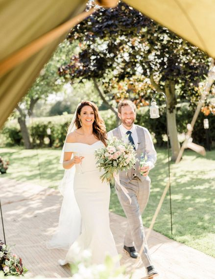 Bride in off the shoulder Pronovias wedding dress and groom in check suit entering the teepee wedding reception