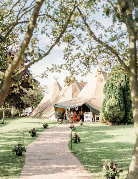 Entrance to teepee wedding reception with flowers and lanterns