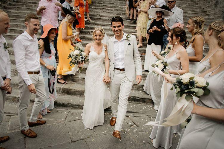 Confetti Moment   Bride in Lace David Fielden Wedding Dress   Groom in Beige Reiss Suit   Monastery Wedding at Monastero San Silvistro Cortona Tuscany   Joe Burford Photography