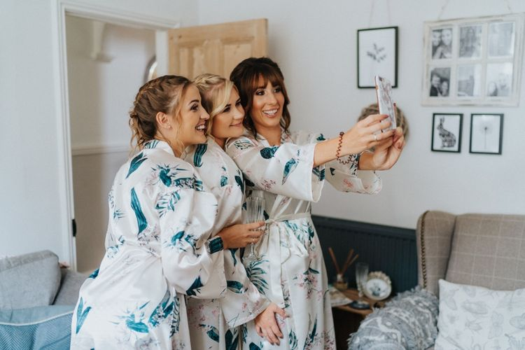 Bridal preparations with bridal party in matching getting ready robes