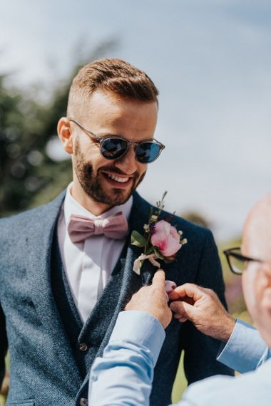 Groom with blush bow tie and floral buttonhole at DIY wedding decor celebration
