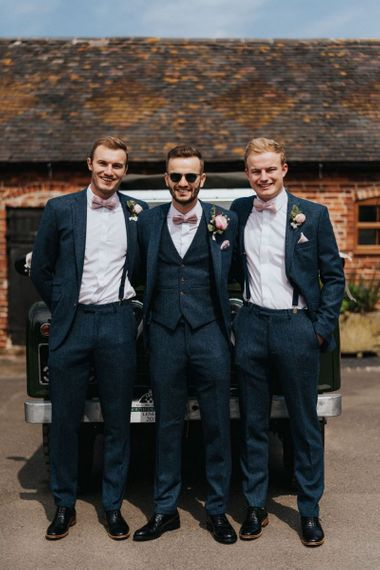 Groom and groomsmen in navy suits with pink buttonholes