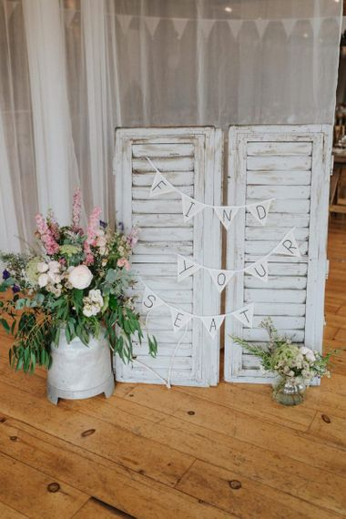 DIY wedding decor with find your seat wedding bunting and flowers in milk churn