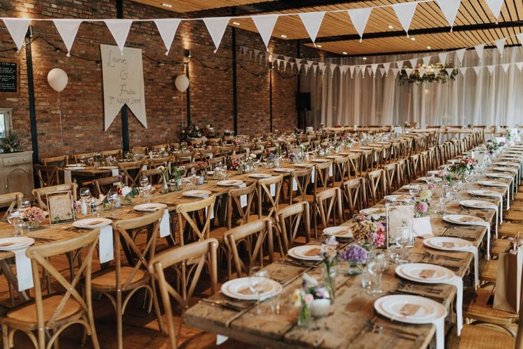 Beautiful rustic wedding setting with pastel flowers with DIY wedding decor and wedding bunting