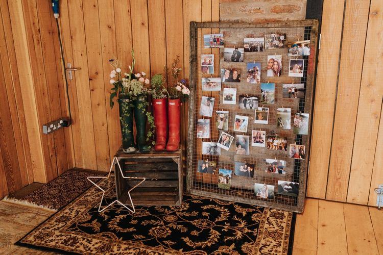 DIY wedding decor with photographs and wellies with flowers in