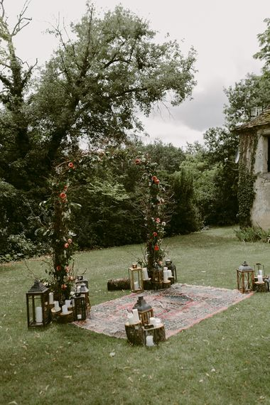Floral Arch, Persian Rug & Lanterns Wedding Decor | Outdoor Boho Wedding at Chateau le Tour, France | Adam and Grace Photography | Head and Heart Films