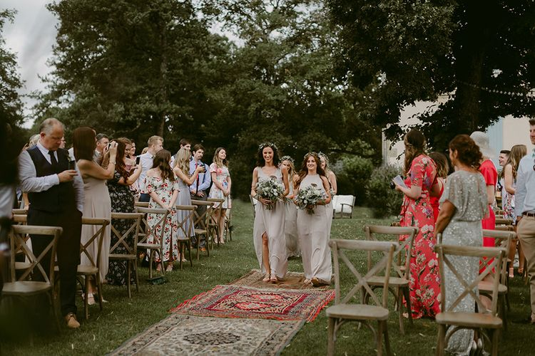 Outdoor Wedding Ceremony | Bridesmaid Entrance in Show me Your Mumu Dresses | Persian Rug, & Floral Arch Aisle & Altar Wedding Decor | Outdoor Boho Wedding at Chateau le Tour, France | Adam and Grace Photography | Head and Heart Films