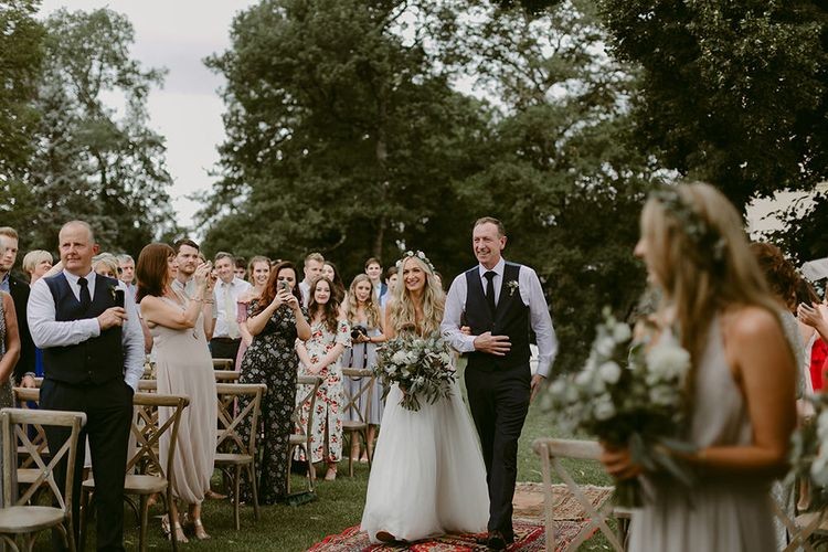Outdoor Wedding Ceremony | Bridal Entrance in Daarlarna Wedding Dress | Persian Rug, & Floral Arch Aisle & Altar Wedding Decor | Outdoor Boho Wedding at Chateau le Tour, France | Adam and Grace Photography | Head and Heart Films