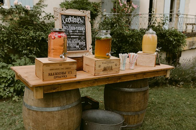 Cocktail Station with Drinks Dispensers | Festoon Lit Outdoor Boho Wedding at Chateau le Tour, France | Adam and Grace Photography | Head and Heart Films