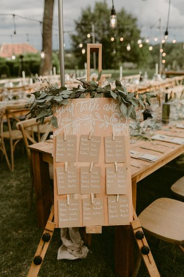 Wooden Table Plan with Greenery Decor | Festoon Lit Outdoor Boho Wedding at Chateau le Tour, France | Adam and Grace Photography | Head and Heart Films