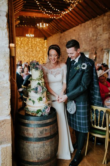 Cutting The Cake // Elegant Scottish Wedding At Kirknewton Stables With Lilac Colour Palette Semi Naked Wedding Cake And Images From Ross Alexander Photography