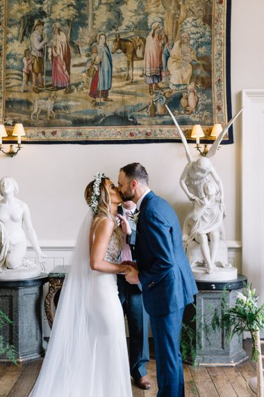 Wedding Ceremony at Elmore Court with Bride in Mikaella Wedding Dress and Groom in Bespoke Navy Check Suit Kissing at the Altar