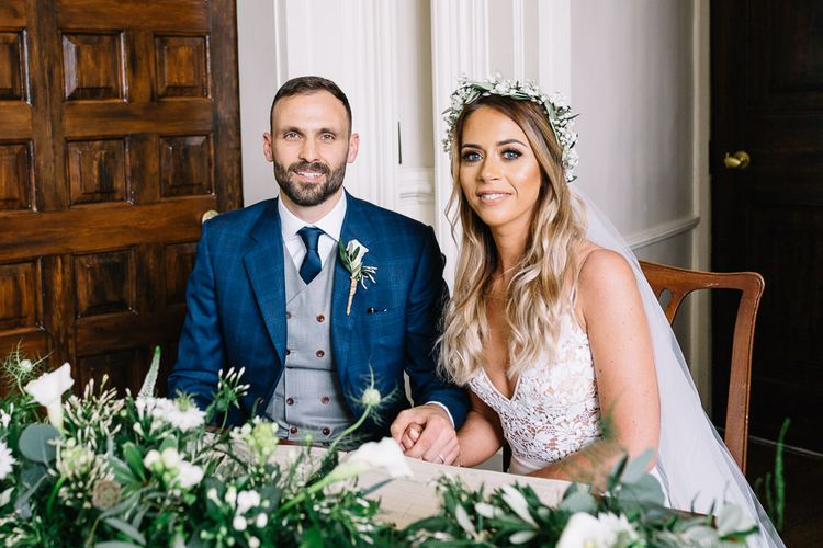 Bride in Mikaella Wedding Dress and Groom in Bespoke Navy Check Suit Signing The Register
