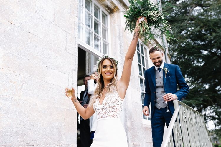 Bride in Fitted Mikaella Wedding Dress with Lace Bodice and Groom in Bespoke Navy Check Suit Exiting the Wedding Ceremony