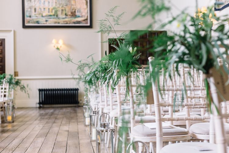 White Aisle Chairs Decorated with Green Foliage
