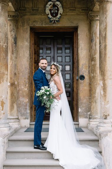 Bride in Fitted Mikaella Wedding Dress with Flower Crown and Groom in Bespoke Navy Check Suit by Territo