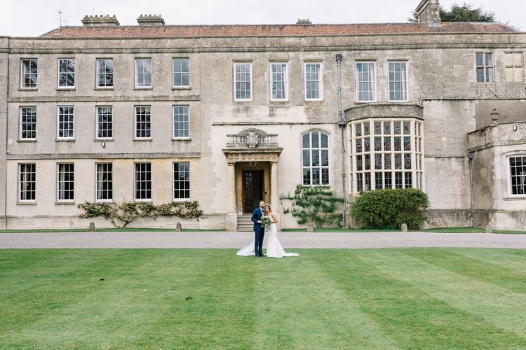 Bride in Fitted Mikaella Wedding Dress with Flower Crown and Groom in Bespoke Navy Check Suit by Territo Standing in Front of Elmore Court